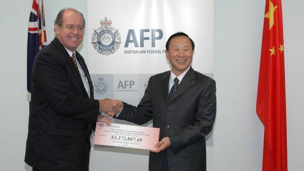 澳大利亚司法和海关部长约翰斯顿(左)向中国公安部副部长张新枫(右)移交赃款(新华社图片7/6/2007)