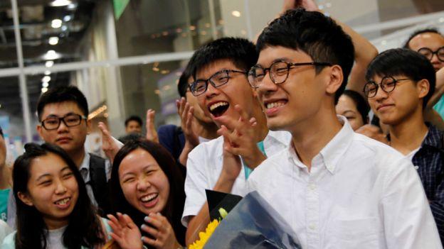 「香港眾志」候選人羅冠聰(圖右)與秘書長黃之鋒(圖左)及支持者們慶祝勝選。