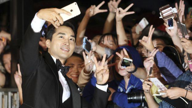 韓國演員宋承憲走紅毯與粉絲自拍。