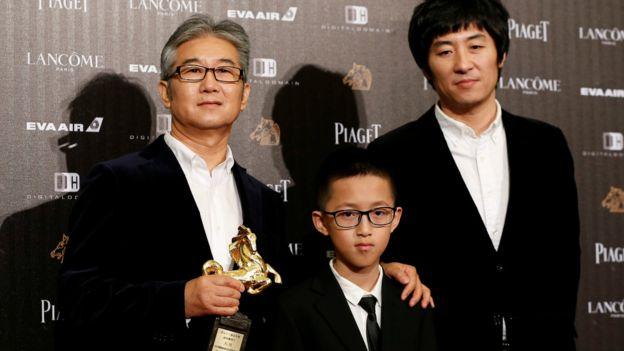 年僅10歲的孔維一(中)與他的父親(左)及《八月》導演張大磊(右)出席金馬獎。