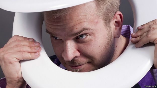Мужчина выглядывает сквозь крышку от унитаза