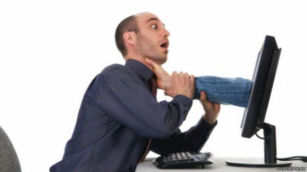 Una mano sale de una pantalla de computadora y toma el cuello de quien está sentado enfrente