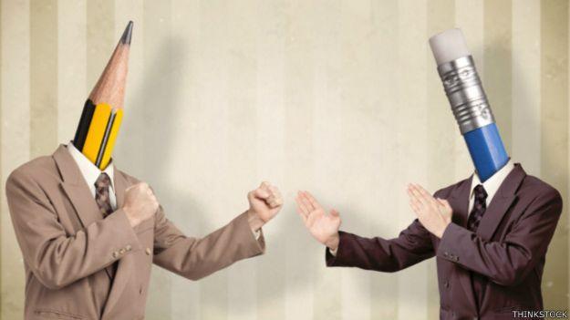 Una persona con cabeza de lápiz y otra con cabeza de bolígrafo pelean