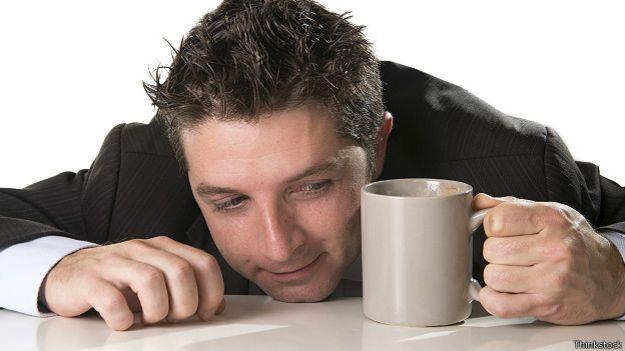Сонный бизнесмен в кружкой кофе