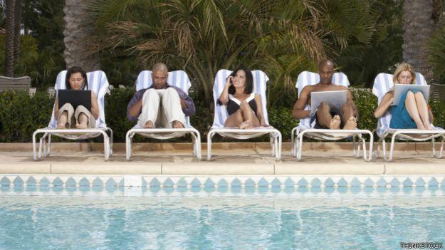 Ejecutivos con laptops frente a una piscina