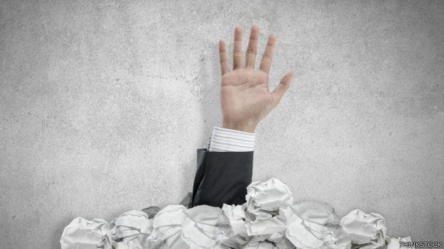 Una mano que sale de una pila de papeles arrugados
