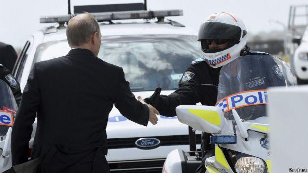 Владимир Путин пожимает руку местному полицейскому накануне отлета с саммита G20 в Брисбене 16 ноября 2014 г.