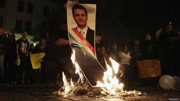 Manifestantes queman una foto del presidente Enrique Peña Nieto