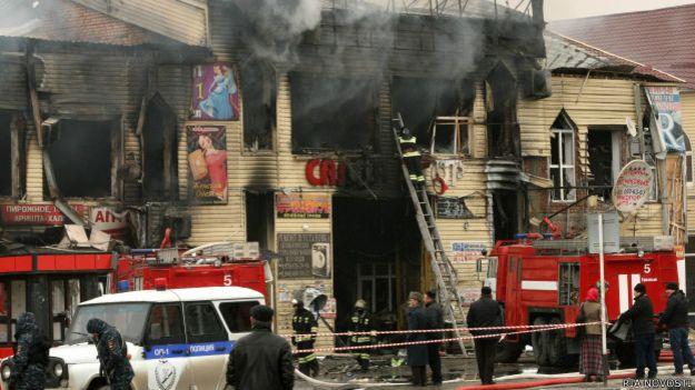 """Пожарные расчеты тушат горящие торговые блоки рынка """"Беркат"""" рядом со зданием Дома печати."""
