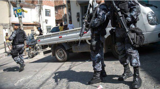 Policías vigilan fuertemente armados en una favela de Brasil.
