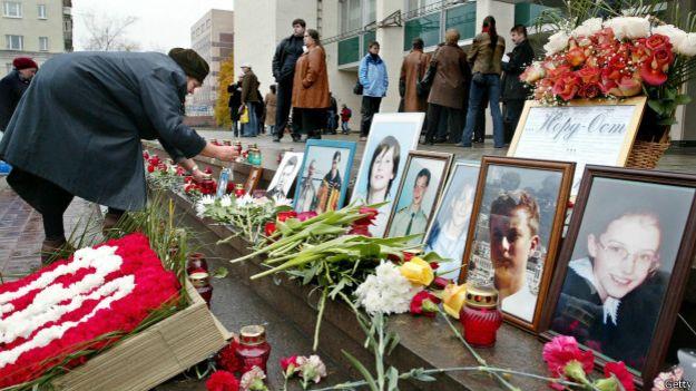 Родственники погибших кладут цветы у входа в здание театра