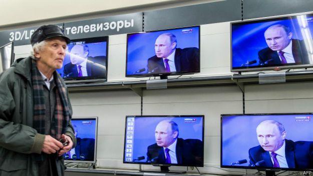 Anciano frente a televisores con Putin