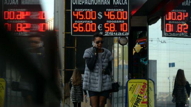 Mujer camina frente casas de cambio