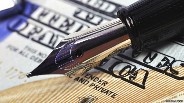 Una pluma fuente sobre un billete de dólar
