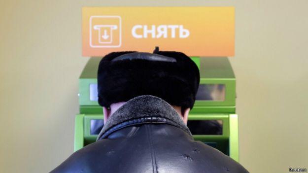 Человек перед банкоматом в отделении Сбербанка
