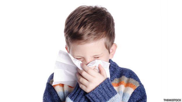 Niño utiliza un pañuelo de papel para soplarse la nariz