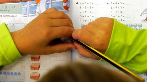 Manos de un niño con un lápiz sobre un cuaderno