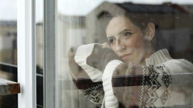 Una mujer hermosa mira a través de una ventana