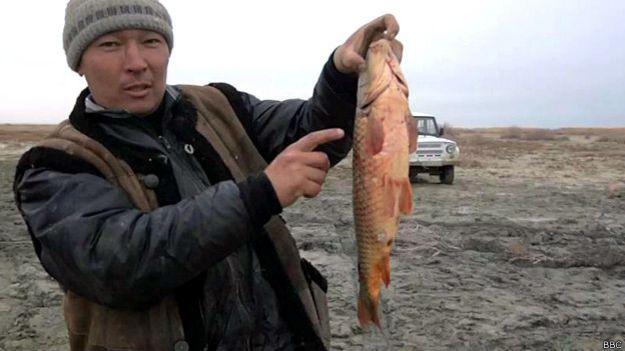 Hombre con un pescado en el mar de Aral