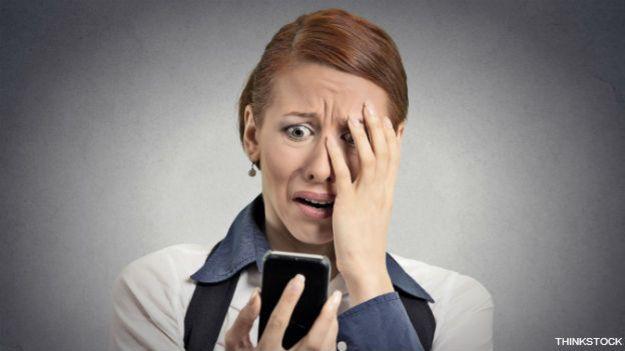 Una ejecutiva horrorizada ante lo que lee en su teléfono inteligente