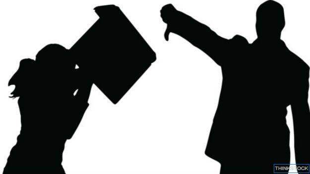 Siluetas de dos empleados peleando computadora en mano