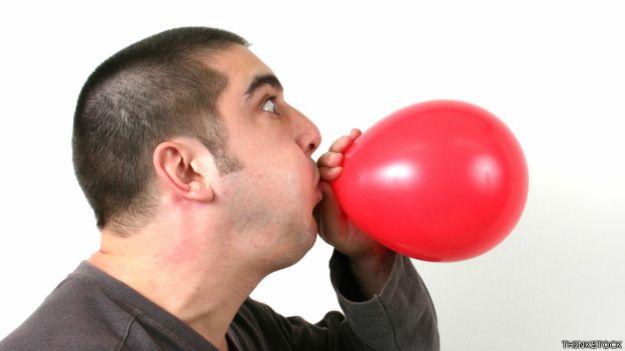 Una persona inflando un globo
