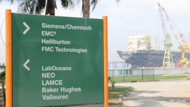 Delante de un barco petrolero, un cartel indica cómo llegar a diferentes empresas del parque tecnológico de la Universidad Federal de Río de Janeiro.