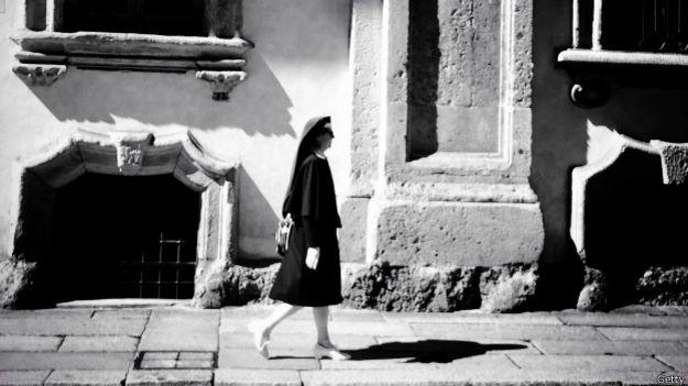 Una religiosa camina por una calle desierta