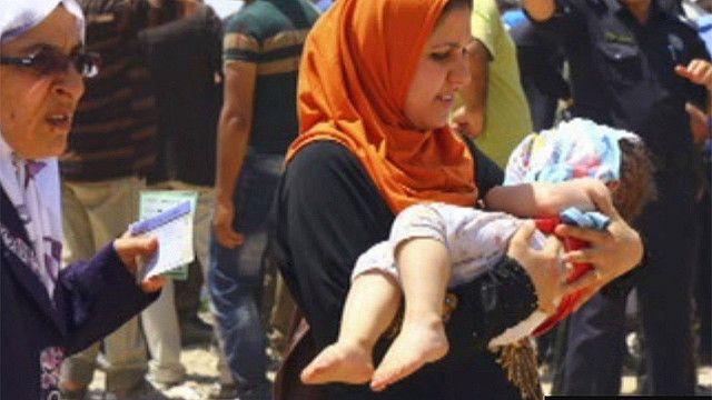 Una madre con su bebé en brazos huyendo de Mosul