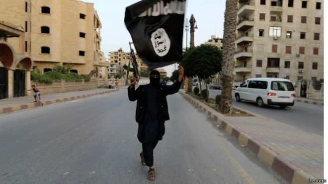 member loyal to the Islamic State in Iraq and the Levant (ISIL) waves an ISIL flag in Raqqa June 29, 2014
