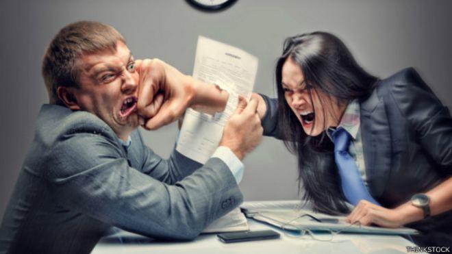 Una persona le da un puñetazo a otra en la oficina
