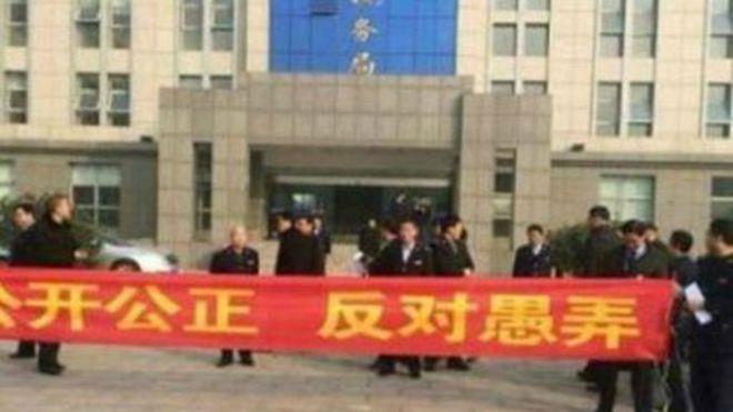 灌云县国税局职工们嫌年新低,拉横幅维权