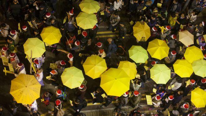 """支持""""占领中环""""运动的示威者在香港铜锣湾举起黄色雨伞游行(24/12/2014)"""