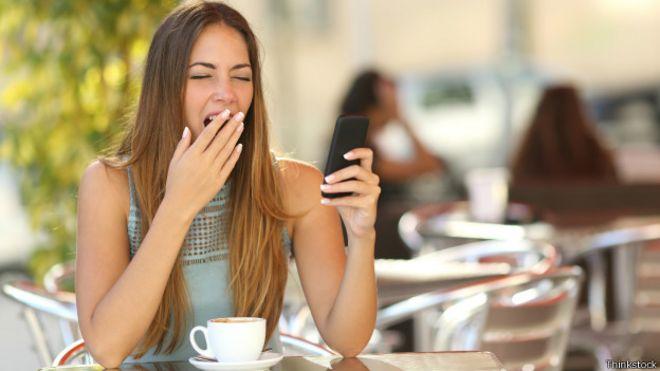 Mujer bostezando mientras ve su celular
