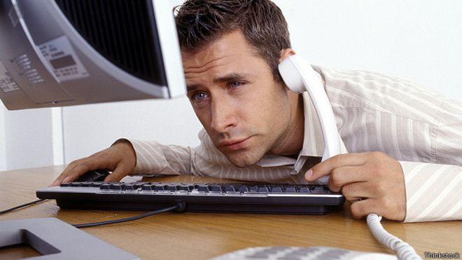 Переутомленный работник перед компьютером
