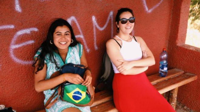 Malika (à esquerda) em um ponto de ônibus de Salvador