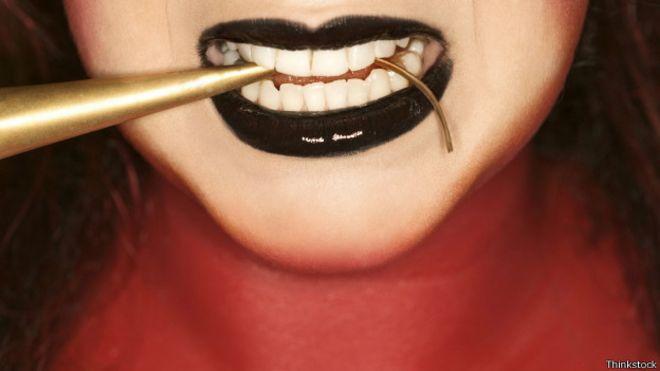 Labios de mujer con un objeto en la boca.