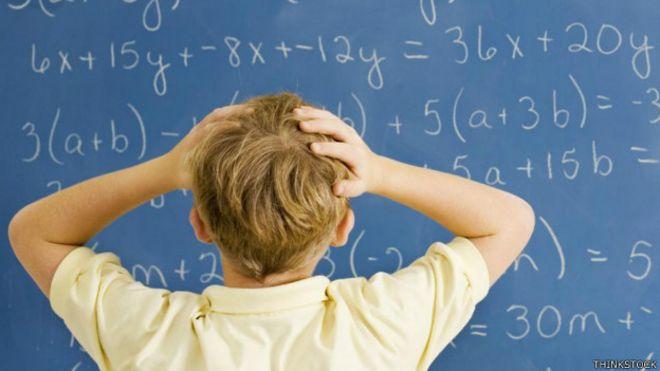 Un niño frente a una pizarra llena de números