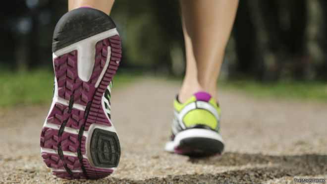 Los pies de un corredor sobre el asfalto