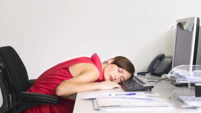 Mujer durmiendo la siesta en la oficina