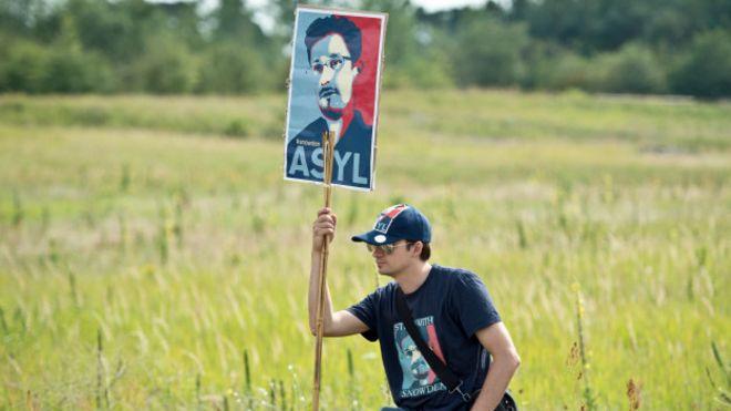 Una persona porta un cartel en apoyo a Edward Snowden
