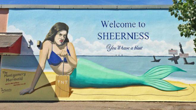 """Un cartel en la localidad de Sherness que dice """"¡puedes pasarlo bomba!"""""""
