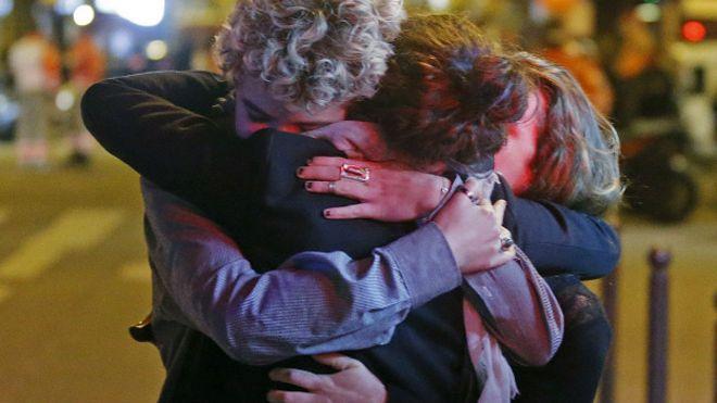 Люди обнимают друг друга рядом с театром