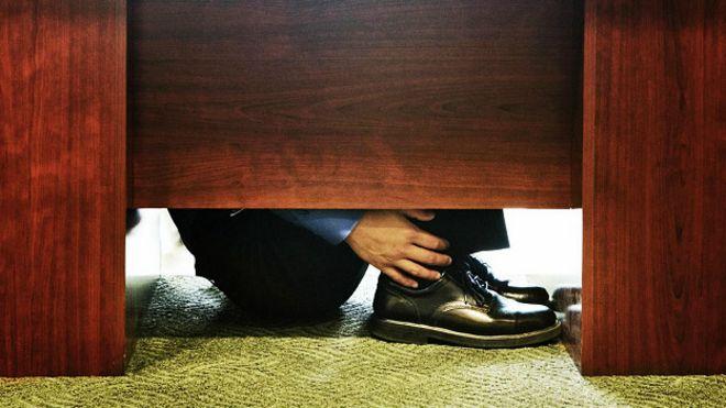 Работник спрятался под стол