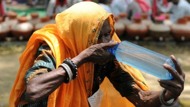 Mujer tomando agua en India