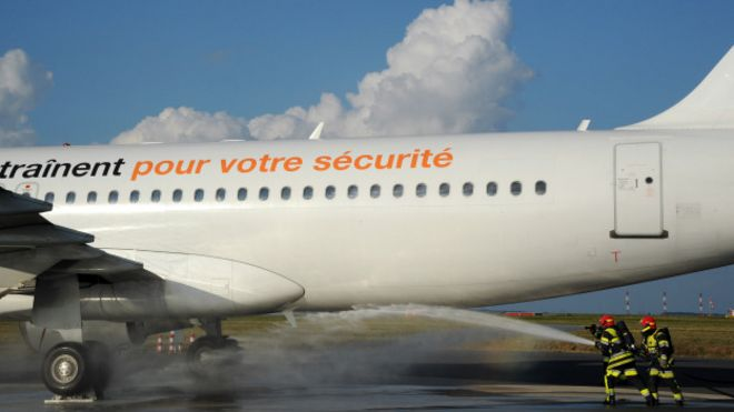 Bomberos sofocando un incendio en el exterior de un avión