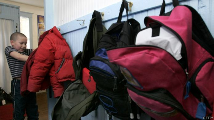 Школьник в раздевалке с рюкзаками