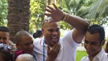St. Louis Cardinals catcher Brayan Pena raises his arm to greet someone as he reunites with family members, including his grandmother Rosa de las Nives, 85, bottom left, at the Hotel Nacional in Havana, Cuba, Tuesday, Dec. 15, 2015