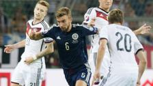 Midfielder James Morrison weaves through the German defence