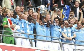 Carlos Tevez lifts the FA Cup, surrounded by his team-mates